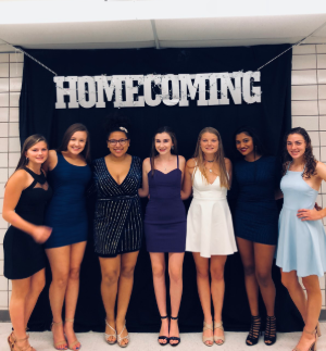 Kelli Mann, Jenna Ptachcinski, Megan Phadael, Olivia LaRosa, Jess Mann, Amala Mammayil, and Nicole Grasso pose in front of the Homecoming sign on Friday night.