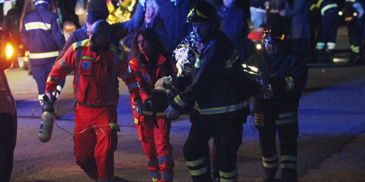 A victim of the stampede at the Italian concert is carried away for severe injuries