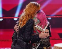 Becky Lynch (left) and Asuka (right) embrace in the ring after Lynch announced her pregnancy Source: essentiallysports.com